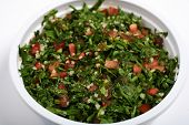 An Arab or Mediterranean tabouleh mezze of parsley, mint, onion, tomatoes, oil and spices, sprinkled