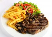 A grilled ribeye steak served with mushrooms,  chips (french fries) and a garden salad of lettuce, c