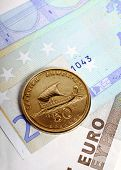 A fifty drachma coin lying on euro notes which replaced the Greek currency. Greece's economic woes a