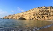 A  view of Matala's famous cliffs and the caves cut into them during the Roman era for use as graves, lit up by the afternoon sun. A handful of latter-day hippies still occupy the caves