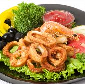Delicious deep fried squid rings with spicy herbs and sauce poster