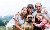 Happy family with a dog enjoying the countryside lifestyle