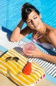 Woman In Pool Relaxing And Drinking