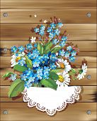 Wooden Illustration with forget-me-not and daisies.