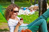 Young woman in dark sunglasses lies in hammock with glass of beverage, pile of garbage in background