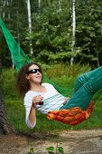Young woman in dark sunglasses lies in hammock with glass of beverage