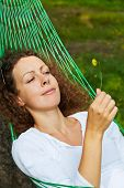 Young woman lies in hammock and looks at yellow flower she holds in her hand