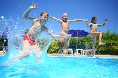 stock photo of boys  - Two little girls and boy fun jumping into the swimming pool - JPG