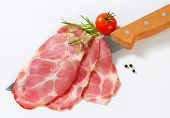 sliced pork neck with tomato, spice and knife