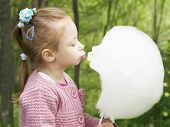 stock photo of candy cotton  - Girl kisses cotton candy in shape of face - JPG