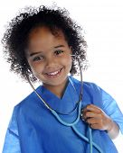 "Portrait of an adorable preschool ""doctor"" in scrubs happily listening to her own heart through a st"