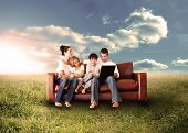 Happy family in the couch using the laptop in a sunny field in the countryside