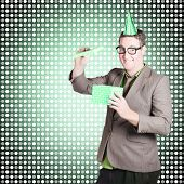 stock photo of dorky  - Comic portrait of a dorky dad opening father day gift box with smile on green dotted background - JPG