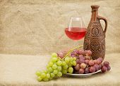 pic of loamy  - Ceramic brown bottle grapes and red wine on sacking - JPG