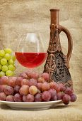 stock photo of loamy  - Ceramic brown bottle grapes and red wine on canvas - JPG