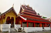 Monks work to resurface the roof and repaint their pagoda