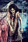 image of terrific  - Bloodthirsty zombi standing at the night cemetery in the mist and moonlight - JPG