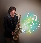 pic of saxophone player  - Attractive young musician playing on saxophone while musical notes exploding - JPG