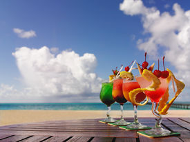 stock photo of summer beach  - four cocktails on the beach on the table - JPG