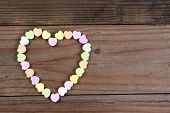 Overhead view of a group of Valentines Day candy on a rustic wood table arranged in a heart shape. H