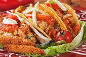 Taco shells filled with grilled chicken meat and fresh vegetable salad
