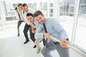 pic of rope pulling  - Full length of a group of business people pulling rope in a bright office - JPG