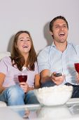 stock photo of wine-press  - Happy young couple with wine glasses and popcorn enjoying a movie on sofa at home - JPG