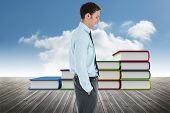 Happy businessman standing with hand in pocket against book steps against sky
