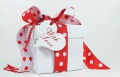 stock photo of special occasion  - Red and white polka dot theme gift box present with heart shape gift tag with love for Christmas Valentine birthday wedding or special occasion - JPG