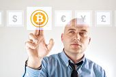 stock photo of bit coin  - Choosing bitoins as currency over other businessman pressing touch screen button - JPG