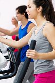 picture of elliptical  - Portrait of young people with elliptic machine in the gym - JPG