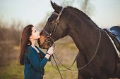 stock photo of bridle  - Young woman with a horse on nature - JPG