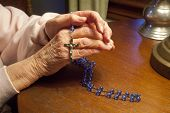 stock photo of rosary  - Elderly hands praying with blue Rosary Beads - JPG