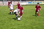Children Playing Soccer In Summer In An Outdoor Grass Arena