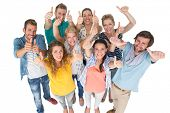 Group portrait of casual cheerful people gesturing thumbs up over white background