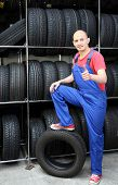 A smiling mechanic in a garage standing next to a rack full of tires and making a positive gesture