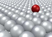 A single red ball lying on a crowd of grey balls.