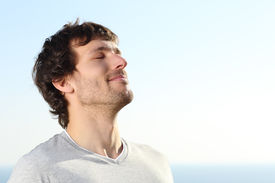 stock photo of breathing exercise  - Close up of a man doing breath exercises outdoor with the sky in the background - JPG