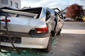 Totaled hatchback motor vehicle after a smash viewed from behind showing a flattened roof and shatte