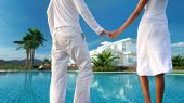 View from behind of a romantic couple standing holding hands overlooking their dream modern whitewas