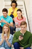 education, leisure and technology concept - busy students with smartphones sitting on staircase