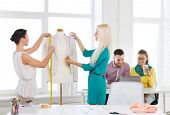 startup, education, fashion and office concept - smiling fashion designers measuring and decorating jacket on mannequin