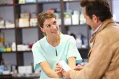 Pharmacist giving advice to customer on medication