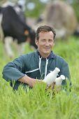 Farmer in field holding bottles of milk