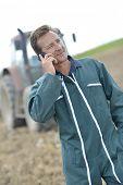 Farmer walking in field and talking on mobile phone