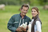 Couple of farmers in field holding milk bottles