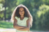 Young girl frowning at camera in the park on a sunny day