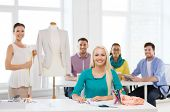 startup, education, fashion and office concept - smiling designers drawing sketches and measuring jacket on mannequin in office