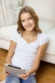 home, technology and internet concept - smiling teenage girl sitting ong the floor with tablet pc co
