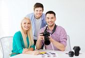 business, education, office and startup concept - smiling creative team with photocamera working in